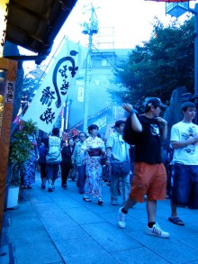 A white banner proudly selling unagi, or eel, to passing festival-goers.